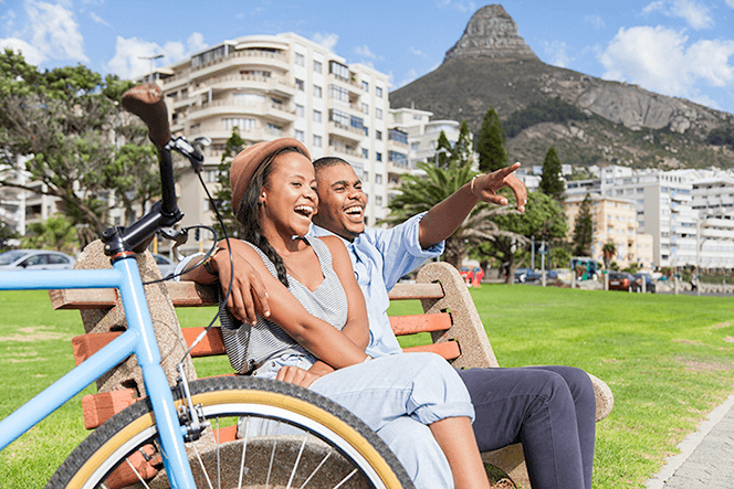 Couple sitting on bench in Cape Town pointing finger