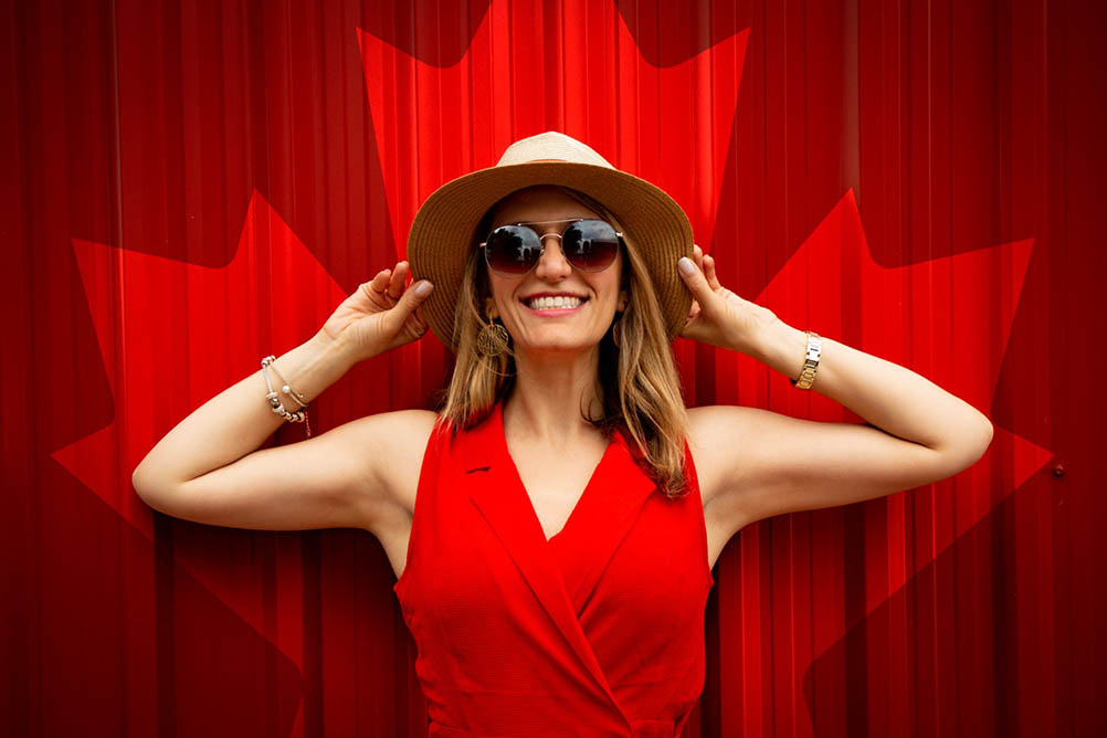 Woman in red smiles while standing in front of a Canadian maple leaf mural