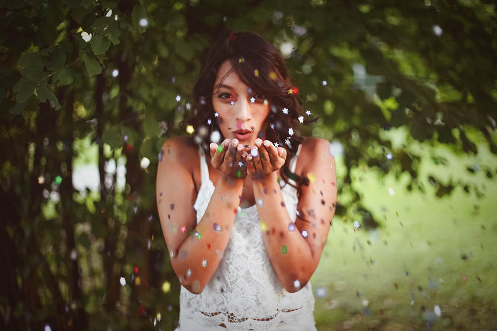 Beautiful woman blows confetti from her hands
