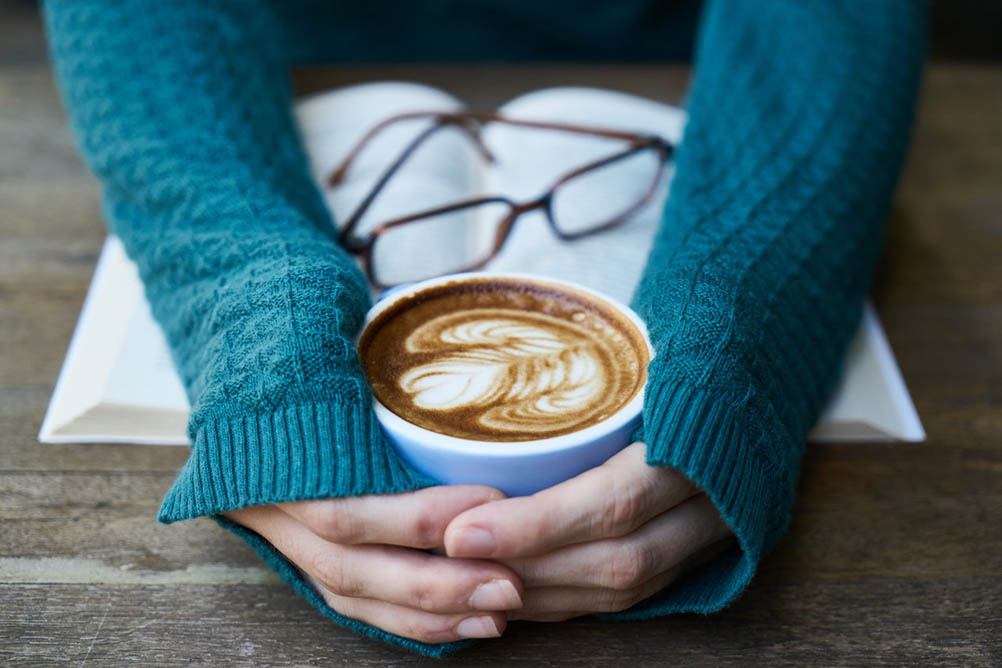 Woman wearing warm jumper clasps a mug of coffee in her hands