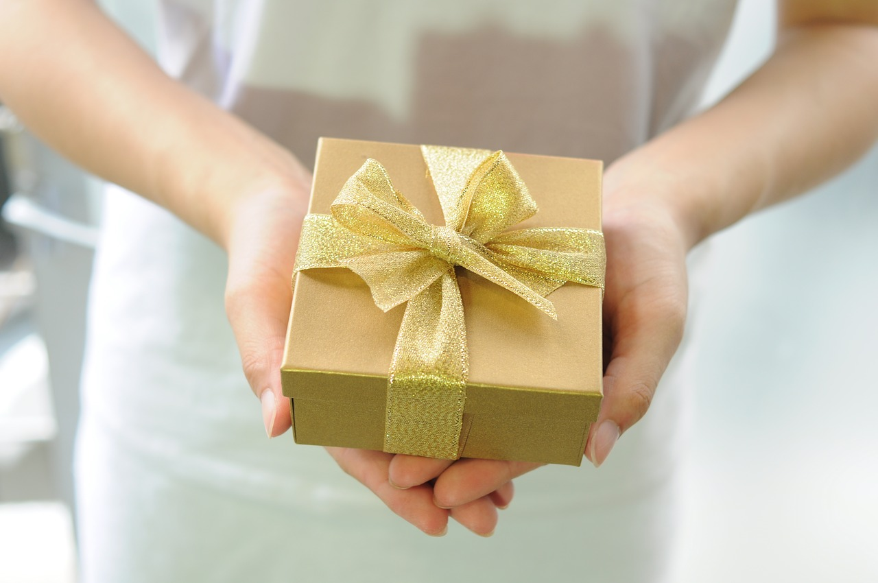 Woman holds a gold-wrapped gift in her outstretched hands.