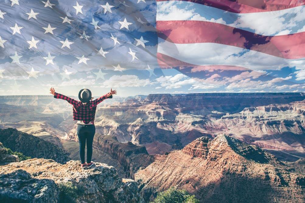 Man celebrates a lottery win on top of a mountain with American flag superimposed on the sky